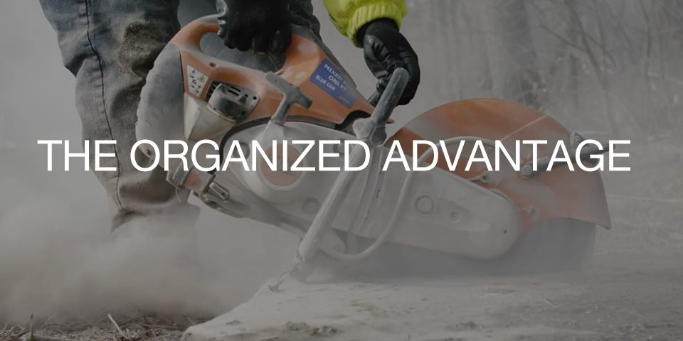 """""""The Organized Advantage"""" Text over image of stone saw"""