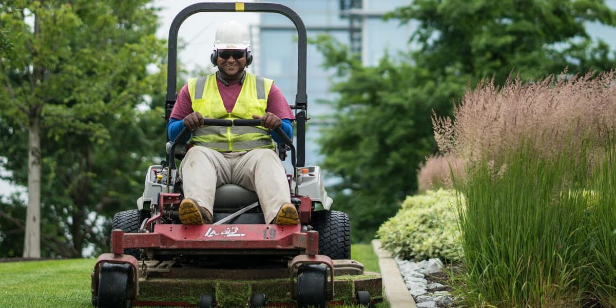 Worker on riding lawnmower, looking happy